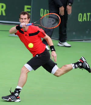Photo - Andy Murray of Great Britain returns the ball to Florian Mayer of Germany during the Qatar ATP Open Tennis tournament in Doha, Qatar, Wednesday, Jan. 1, 2014. (AP Photo/Osama Faisal)