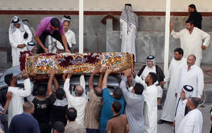 Photo - Mourners unload the coffin of Imad Younis, 22, who was killed in a car bomb attack, in the Shiite holy city of Najaf, 100 miles (160 kilometers) south of Baghdad, Iraq, Thursday, Aug. 15, 2013. A wave of car bombs  on Wednesday killed and wounded dozens of people, the latest attacks in a months-long surge in violence. More than 3,000 people have been killed in violence during the past few months, raising fears Iraq could see a new round of widespread sectarian bloodshed similar to that which brought the country to the edge of civil war in 2006 and 2007. (AP Photo/Haider Hamdani)