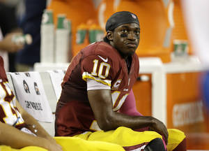 Photo - Washington Redskins quarterback Robert Griffin III (10) sits on the bench in the second half of an NFL football game against the Dallas Cowboys, Sunday, Oct. 13, 2013, in Arlington, Texas. (AP Photo/LM Otero)