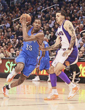 photo - Kevin Durant, left, drives to the basket against Phoenix forward Matt Barnes during the Thunder's 140-118 loss Friday. Durant scored 35 points and had eight rebounds and five assists in the loss. Ap photo
