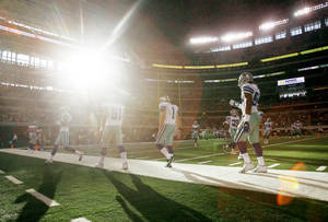 Photo - The Dallas Cowboys warm up on the field as the sun peeks through the glass wall before the start of  Friday's preseason game against Tennessee. AP Photo