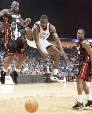Photo - Oklahoma City's Jeff Green, center, loses control of the ball after a foul between Miami's Joel Anthony, left, and Mario Chalmers.  Photo by Bryan Terry, The Oklahoman