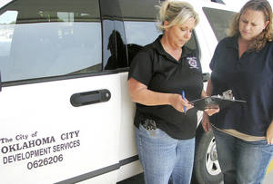 Photo - Code enforcement officer Tammie Brimm looks over a sheet of complaints with trainee Theresa Samples in July in Oklahoma City. Photo by Vallery Brown, The Oklahoman