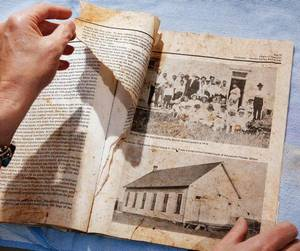 Photo - Sheila Rose found this wet and dirty book in her back yard Tuesday evening while cleaning up storm debris at her Midwest City home. The old book is about the early history of Chickasha. <strong>JIM BECKEL - THE OKLAHOMAN</strong>