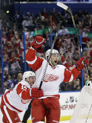 Photo - Detroit Red Wings defenseman Kyle Quincey (27) celebrates his goal with teammate Gustav Nyquist (14), of Sweden, after scoring against the Tampa Bay Lightning during the first period of an NHL hockey game Thursday, Dec. 12, 2013, in Tampa, Fla. (AP Photo/Chris O'Meara)