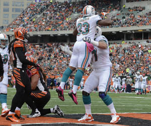 Photo -   Miami Dolphins running back Daniel Thomas (33) jumps in the arms of tackle Jake Long after Thomas scored a touchdown in the first half of an NFL football game against the Cincinnati Bengals, Sunday, Oct. 7, 2012, in Cincinnati. (AP Photo/Michael Keating)