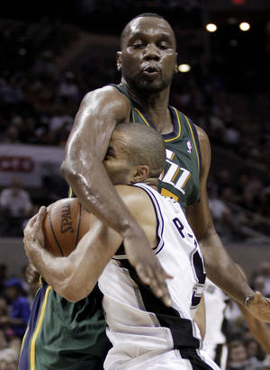 photo -   San Antonio Spurs' Tony Parker, front, of France, is fouled by Utah Jazz's Al Jefferson during the third quarter of Game 2 of a first-round NBA basketball playoff series, Wednesday, May 2, 2012, in San Antonio. (AP Photo/Eric Gay)