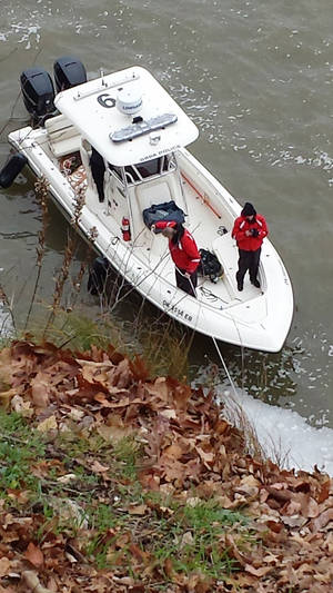 Photo - Grand River Dam Authority police officers wait on their boat as divers search for a vehicle that plunged into Grand Lake on Friday. PHOTO BY GARY CROW, FOR THE OKLAHOMAN <strong>Gary Crow</strong>
