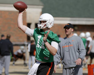 Photo - Oklahoma State quarterback Wes Lunt throws a pass as offensive coordinator Mike Yurcich watches during an OSU spring football practice in Stillwater, Okla., Wednesday, March 13, 2013. Photo by Bryan Terry, The Oklahoman