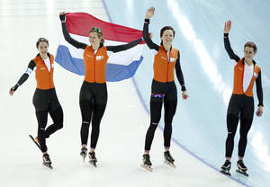 Photo - Marrit Leenstra, Lotte van Beek, Jorien ter Mors, and Ireen Wust of the Netherlands celebrate with the national flag after taking the gold medal on the women's team pursuit at the Adler Arena Skating Center at the 2014 Winter Olympics, Saturday, Feb. 22, 2014, in Sochi, Russia. (AP Photo/Pavel Golovkin)