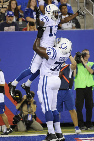 Photo - Indianapolis Colts wide receiver T.Y. Hilton celebrates with teammate Gosder Cherilus (78) after scoring a touchdown during the first half of an NFL preseason football game, Sunday, Aug. 18, 2013, in East Rutherford, N.J. (AP Photo/Bill Kostroun)
