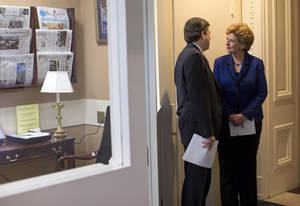 Photo - Sen. Debbie Stabenow, D-Mich., right, talks with Sen. Mark Begich, D-Alaska, before a news conference on Capitol Hill in Washington, Wednesday, Dec. 5, 2012, where they discussed the debate on tax rates and the fiscal cliff.  (AP Photo/ Evan Vucci)