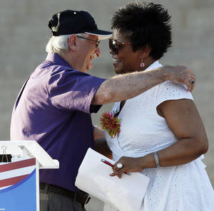 Photo - State Rep. Paul Wesselhoft, R-Moore, left, hugs state Sen. Constance Johnson, D-Forest Park, during a nonpartisan rally against the United States' involvement in the Syrian civil war, on the south side of state Capitol in Oklahoma City, on Friday. Photo by Nate Billings, The Oklahoman <strong>NATE BILLINGS</strong>