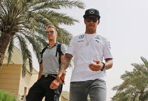 Photo - British Formula One driver Lewis Hamilton of Mercedes AMG Petronas, right, arrives at the circuit ahead of the Bahrain Formula One Grand Prix at the Formula One Bahrain International Circuit in Sakhir, Bahrain, Thursday, April 3, 2014. The Bahrain Formula One Grand Prix will take place at the circuit on Sunday. (AP Photo/Kamran jebreili)