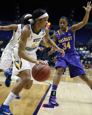 Photo - West Virginia guard Christal Caldwell (1) dribbles past Albany guard Cassandra Edwards (34) in the first half of an NCAA college basketball first-round tournament game on Sunday, March 23, 2014, in Baton Rouge, La. West Virginia won 76-61. (AP Photo/Rogelio V. Solis)