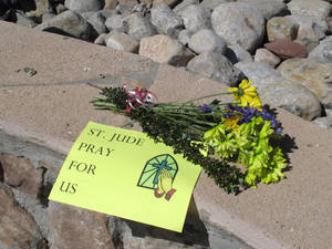 Photo - A sign and flowers are left by a parishioner at the St. Jude Thaddeus Catholic Church in Albuquerque Monday, April 29, 2013, a day after a man stabbed several churchgoers Sunday as Mass was ending. Police say four parishioners were injured, including church choir director Adam Alvarez, but none have life-threatening injuries. Lawrence Capener, 24, is charged with three counts with aggravated battery and is being held on $75,000 bail.  (AP Photo/Russell Contreras)