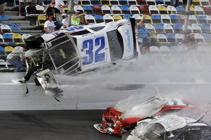 Photo - Kyle Larson (32) goes airborne and into the catch fence during a multi-car crash involving Justin Allgaier (31), Brian Scott (2) and others during the final lap of the NASCAR Nationwide Series auto race at Daytona International Speedway, Saturday, Feb. 23, 2013, in Daytona Beach, Fla.  Larson's crash sent car parts and other debris flying into the stands injuring spectators. (AP Photo/John Raoux)