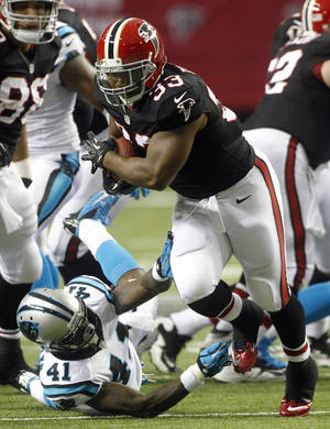 photo -   Atlanta Falcons running back Michael Turner (33) runs out of the tackle of Carolina Panthers cornerback Captain Munnerlyn (41)during the first half of an NFL football game Sunday, Sept. 30, 2012, in Atlanta. (AP Photo/John Bazemore)