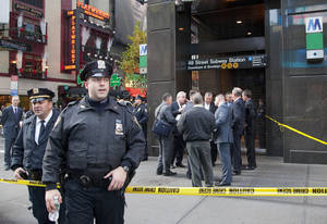 Photo - Uniformed and plainclothes police officers stand outside a New York subway station after a man was killed after falling into the path of a train, Monday, Dec. 3, 2012. Transit officials say police are investigating whether he could have been pushed onto the tracks. (AP Photo/Mark Lennihan)