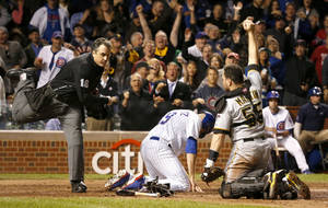 Photo - Home plate umpire Mike DiMuro calls Chicago Cubs' Nate Schierholtz out at home as Pittsburgh Pirates catcher Russell Martin shows DiMuro the ball during the ninth inning of a baseball game Monday, Sept. 23, 2013, in Chicago. The Pirates won 2-1. (AP Photo/Charles Rex Arbogast)