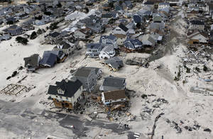 Photo - FILE - In this Oct. 31, 2012 file photo, a view from the air shows the destroyed homes left in the wake of Superstorm Sandy in Seaside Heights, N.J. New Jersey got the brunt of Sandy, which made landfall in the state and killed six people. A presidential task force charged with developing a strategy for rebuilding coastal areas damaged by Sandy will issue a report on Monday, Aug. 19, 2013, recommending 69 measures that might help insure that coastal areas aren't as vulnerable to future storms in an age of rising sea levels. (AP Photo/Mike Groll, File)
