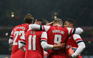 Photo - Arsenal's Lukas Poldoski, No 9, celebrates with teammates after scoring the opening goal during their fourth round English FA Cup soccer match between Arsenal and Coventry City at the Emirates stadium in London, Friday, Jan.  24, 2014. (AP Photo/Alastair Grant)