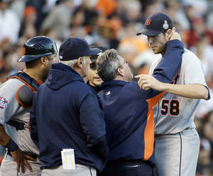 Photo -   A trainer looks at Detroit Tigers starting pitcher Doug Fister after getting hit by a ball off the bat of San Francisco Giants' Gregor Blanco during the second inning of Game 2 of baseball's World Series Thursday, Oct. 25, 2012, in San Francisco. (AP Photo/David J. Phillip)