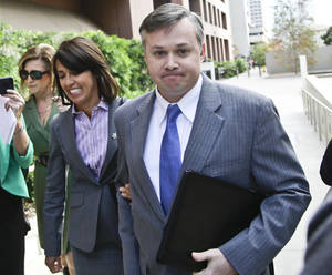 John Beliveau II, accompanied by attorney Gretchen von Helms, arrives at the federal courthouse, Wednesday Dec. 17, 2013, in San Diego, where Beliveau is expected to plead guilty on bribery charges in connection with the over billing of the U.S. Navy of millions of dollars. (AP Photo/Lenny Ignelzi)