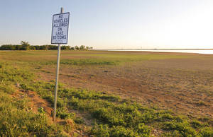"Photo -  A ""No Vehicles Allowed on Lake Bottom"" sign is posted Friday at what should be the shoreline when Lake Hefner is full in Oklahoma City. Photo by Paul B. Southerland, The Oklahoman  <strong>PAUL B. SOUTHERLAND -   </strong>"