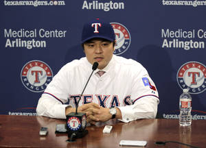 Photo - Shin-Soo Choo, of South Korea, answers questions during a news conference announcing his signing to the Texas Rangers, Friday, Dec. 27, 2013, in Arlington, Texas. Choo was signed to a $130 million, seven-year contract. (AP Photo/Tim Sharp)