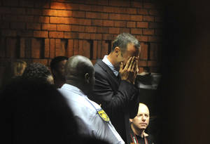 photo - Athlete Oscar Pistorius weeps in court in Pretoria, South Africa, Friday, Feb 15, 2013, at his bail hearing in the murder case of his girlfriend Reeva Steenkamp.   Oscar Pistorius arrived at a courthouse Friday, for his bail hearing in the murder case of his girlfriend as South Africans braced themselves for the latest development in a story that has stunned the country. The Paralympic superstar was earlier seen leaving a police station in a dark suit with a charcoal gray jacket covering his head as he got into a police vehicle. Model Reeva Steenkamp was shot and killed at Pistorius' upmarket home in an eastern suburb of the South African capital in the predawn hours of Thursday. (AP Photo/Antione de Ras - Independent Newspapers Ltd South Africa) SOUTH AFRICA OUT