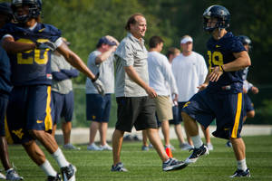 photo - West Virginia University college football head coach Dana Holgorsen, center, watches his team run drills during NCAA college football practice in Morgantown, W.Va. on Friday, August 5, 2011. (AP Photo/David Smith) ORG XMIT: WVDS104