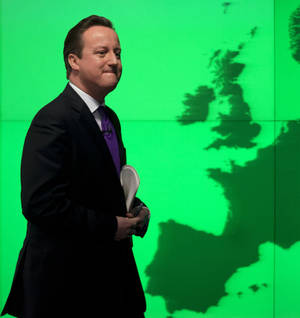 "Photo - Britain's Prime Minister David Cameron walks past a map of Europe on a screen as he walks away after making a speech on holding a referendum on staying in the European Union in London, Wednesday, Jan. 23, 2013. Cameron said Wednesday he will offer British citizens a vote on whether to leave the European Union if his party wins the next election, a move which could trigger alarm among fellow member states. He acknowledged that public disillusionment with the EU is ""at an all-time high,"" using a long-awaited speech in central London to say that the terms of Britain's membership in the bloc should be revised and the country's citizens should have a say. (AP Photo/Matt Dunham)"