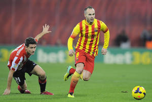 Photo - Barcelona's Andres Iniesta, right, duels for the ball with Athletic Bilbao's Ander Herrera during their Spanish League soccer match, at San Mames stadium in Bilbao, Spain, Sunday, Dec. 1, 2013. (AP Photo/Alvaro Barrientos)