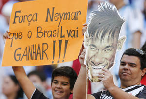 """Photo - Fans hold a cutout showing Brazilian player Neymar with a sign that reads in Portuguese '""""Strength Neymar,  Brazil will win,"""" before the World Cup quarterfinal soccer match between Argentina and Belgium at the Estadio Nacional in Brasilia, Brazil, Saturday, July 5, 2014. Neymar, the biggest football star in Brazil, was ruled out of the rest of the tournament after fracturing his third vertebra during Friday's 2-1 quarterfinal win over Colombia. (AP Photo/Eraldo Peres)"""