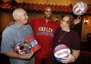 Photo - Harlem Globetrotter Flight Time Lang poses for a photo with George and Lin Wilson. Their first date as a married couple was to a Globetrotter game in 1963. Photos By Steve Gooch, The Oklahoman