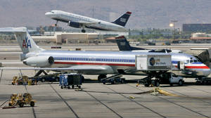 photo - FILE - In this June 23, 2008 file photo, a US Airways jet takes off as an American Airlines jet is prepped for takeoff at Sky Harbor International Airport in Phoenix. The merger of US Airways and American Airlines has given birth to a mega airline with more passengers than any other in the world. (AP Photo/Matt York, File)