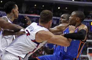 Photo - Los Angeles Clippers forward Matt Barnes, left and Clippers forward Blake Griffin, second from left, tangle with Oklahoma City Thunder forward Serge Ibaka, second from right, of Congo, and Thunder guard Russell Westbrook, right, in the first half of their NBA basketball game Wednesday, Nov. 13, 2013, in Los Angeles. Ibaka and Barnes were ejected from the game after the scuffle. (AP Photo/Alex Gallardo)