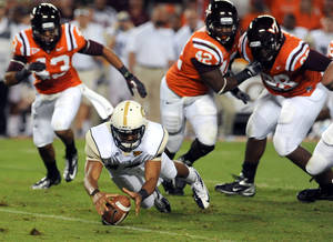 photo -   Georgia Tech quarterback Tevin Washington dives on the ball to regain possession while under pressure from Virginia Tech outside linebacker Jeron Gouveia-Winslow and defensive end J.R. Collins (42) during the first half of an NCAA college football game, Monday, Sept. 3, 2012, in Blacksburg, Va. (AP Photo/Don Petersen)  