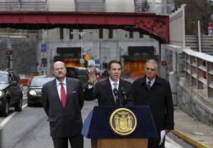 Photo -   New York Governor Andrew Cuomo, center, speaks at a news conference while United States Secretary of Transportation Ray LaHood, right, and MTA Chairman Joseph Lhota look on in front of the Hugh L. Carey Tunnel, formerly the Brooklyn-Battery Tunnel, in New York, Tuesday, Nov. 13, 2012. Cuomo announced the the tunnel, which was closed from damage caused by Superstorm Sandy, will open to limited traffic. (AP Photo/Seth Wenig)