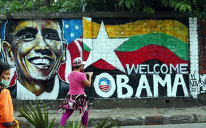 "Photo -   A woman takes a photo of a wall painting created by Myanmar graffiti artists to welcome U.S. President Barack Obama on a street in Yangon, Myanmar, Saturday, Nov. 17, 2012. Obama will visit Myanmar on Monday, in a first for a sitting U.S. president. White House officials on Thursday said he will use his visit ""to lock down progress and to push on areas where progress is urgently needed"" — most notably freeing political prisoners and ending ethnic tensions in the western state of Rakhine and the northern state of Kachin. Obama's stop in Myanmar, scheduled to last about six hours, is the centerpiece of his first foreign tour since winning re-election. (AP Photo)"