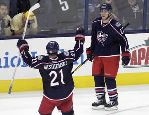 Photo - Columbus Blue Jackets' Ryan Murray, right, celebrates his game-winning goal against the Pittsburgh Penguins with teammate James Wisniewski during the overtime period of an NHL preseason hockey game, Sunday, Sept. 15, 2013, in Columbus, Ohio. The Blue Jackets beat the Penguins 5-4. (AP Photo/Jay LaPrete)