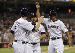 Photo -   San Diego Padres' Chase Headley, left, and Will Venable, right, congratulate Yonder Alonso, center, for hitting a grand slam home run against the Colorado Rockies during the first inning of their baseball game in San Diego, Calif., Friday, Sept. 14, 2012. (AP Photo/Alex Gallardo)