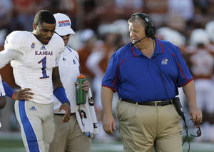 Photo - Kansas coach Charlie Weis, right, talks with receiver Rodriguez Coleman (1) after he was injured during the second half of an NCAA college football game against Texas, Saturday, Nov. 2, 2013, in Austin, Texas. Texas won 35-13. (AP Photo/Eric Gay)