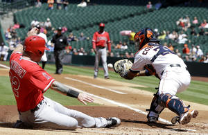 Photo - Los Angeles Angels' Josh Hamilton (32) slides into home to score as Houston Astros catcher Carlos Corporan (22) reaches for the ball in the first inning of a baseball game Monday, April 7, 2014, in Houston. Hamilton and Albert Pujols scored on a Howie Kendrick single. (AP Photo/Pat Sullivan)