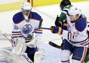 Photo - Edmonton Oilers goalie Ilya Bryzgalov (80) of Russia makes a stop as teammate Andrew Ference (21) ties up Dallas Stars left wing Ray Whitney during the first period of an NHL hockey game Sunday, Dec. 1, 2013, in Dallas.  (AP Photo/LM Otero)