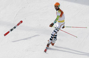 Photo - Germany's Stefan Luitz arrives in the finish area on one ski after hitting a gate in the first run of the men's giant slalom at the Sochi 2014 Winter Olympics, Wednesday, Feb. 19, 2014, in Krasnaya Polyana, Russia.  (AP Photo/Gero Breloer)