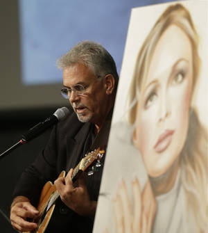 Photo - Michael Inge, stepfather of country music star Mindy McCready, plays a song during the funeral ceremony at the Crossroads Baptist Church in Fort Myers, Fla., Tuesday, Feb. 26, 2013.  McCready committed suicide Feb. 17 at her home in Arkansas, days after leaving a court-ordered substance abuse program. (AP Photo/Alan Diaz)
