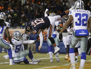 Photo - Chicago Bears quarterback Josh McCown (12) gets hit by Dallas Cowboys linebacker Sean Lee (50) in the air as McCown makes a touchdown run during the first half of an NFL football game, Monday, Dec. 9, 2013, in Chicago. (AP Photo/Nam Y. Huh)