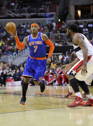 Photo - New York Knicks forward Carmelo Anthony (7) brings the ball upcourt against Washington Wizards forward Nene, right, of Brazil, during the first half of an NBA basketball game on Saturday, Nov. 23, 2013, in Washington. (AP Photo/Nick Wass)